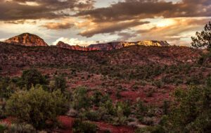 A photograph of the Sedona red rocks under a stormy sunset.