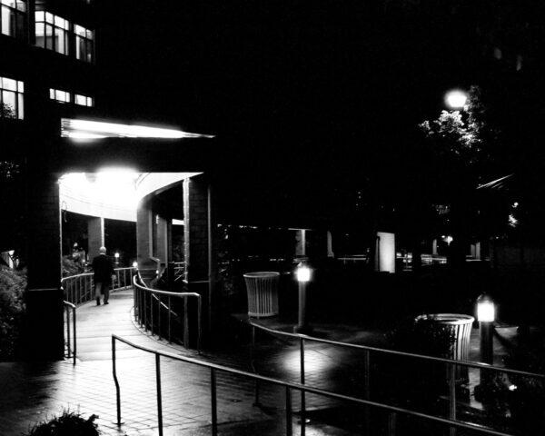 A nighttime photograph of a man walking.