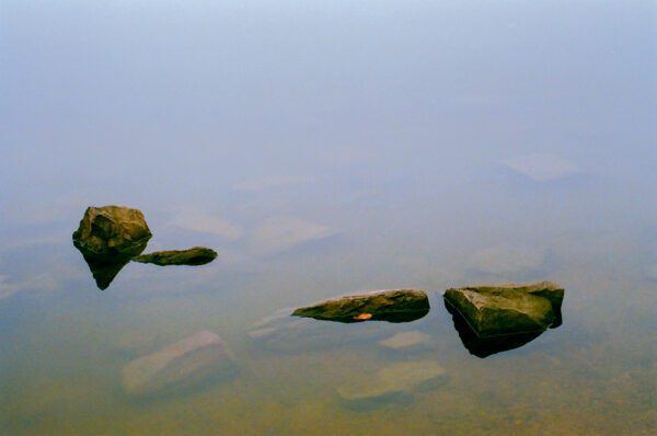 A film photograph of rocks in water