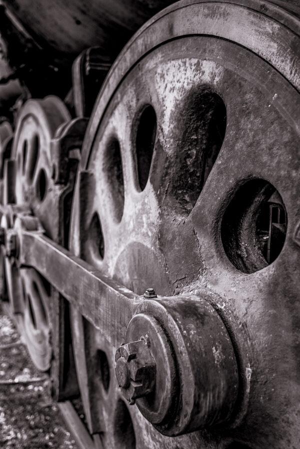A close-up photograph of an antique train wheel.