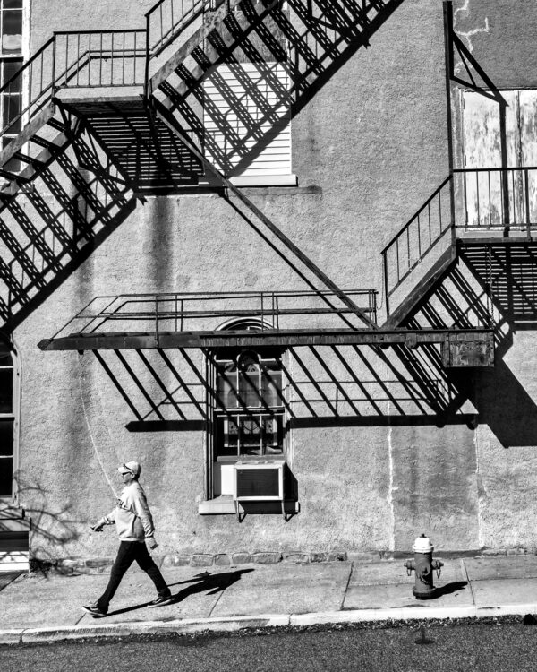 photo of a man walking by a wall with fire escapes