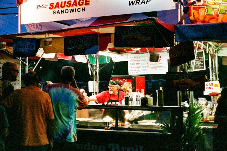 Man servicing sausage sandwiches at Musicfest